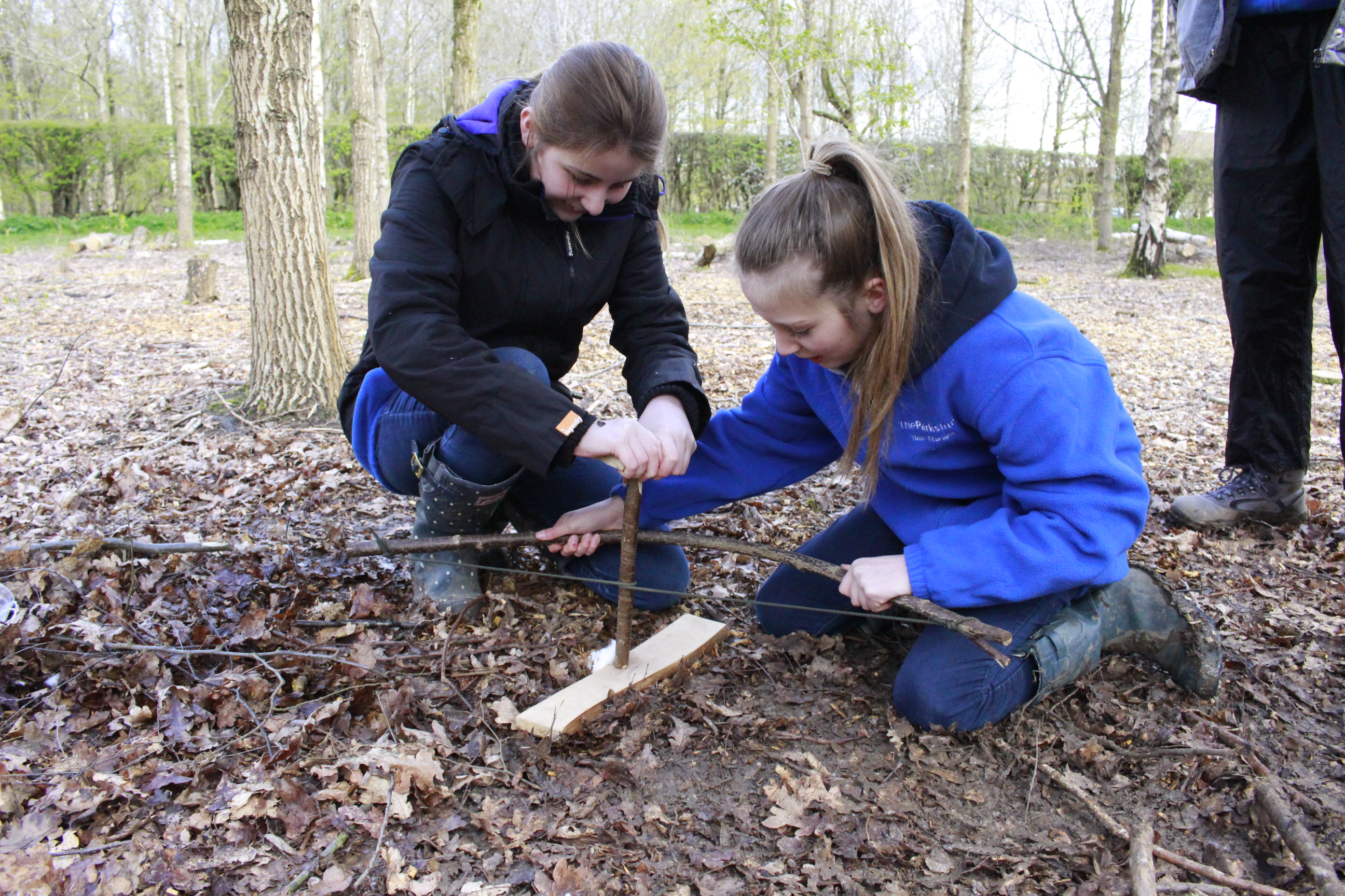 Two girls learning to light a fire using the friction method with a bow and drill